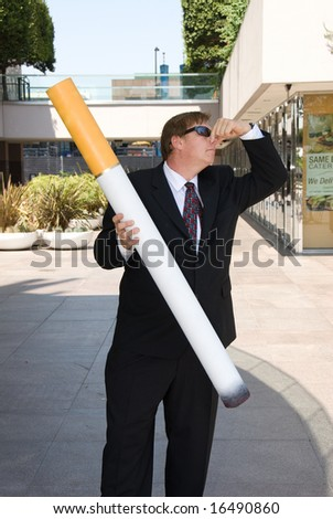 A man symbolizes an anti-smoking gesture by plugging his nose while holding a large prop cigarette.