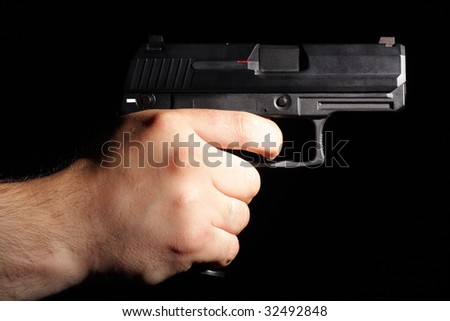 A man tacking aim. Pistol in man hand isolated on black.