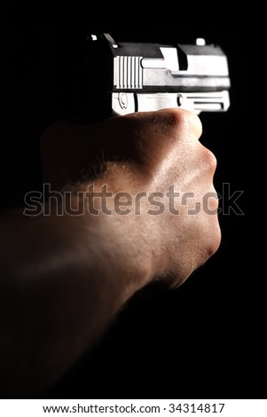 A man tacking aim. Pistol in man hand, isolated on black. Shallow DOF!