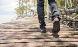 A man Take a walk on a wooden bridge along the seashore.Men wear shoes and Jeans walk out on a wooden bridge alone.
