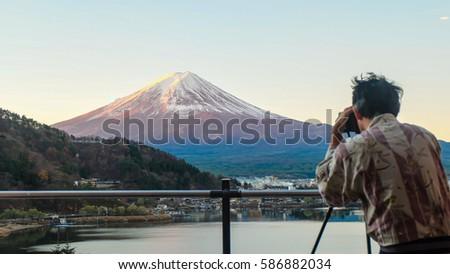 A man take photo on mountain Fuji at Kawaguchiko lake in japan with blue cloud sky