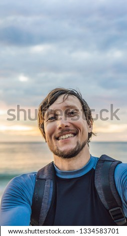 A man takes a selfie on the background of the sea and sunset VERTICAL FORMAT for Instagram mobile story or stories size. Mobile wallpaper