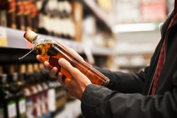 A man takes alcoholic drinks from the supermarket shelf. Shopping for alcohol in the store.
