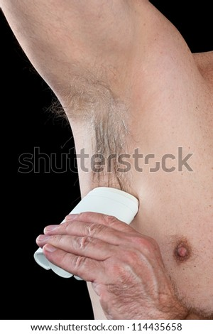 A man takes care of his hygiene by applying deodorant to his hairy armpit.