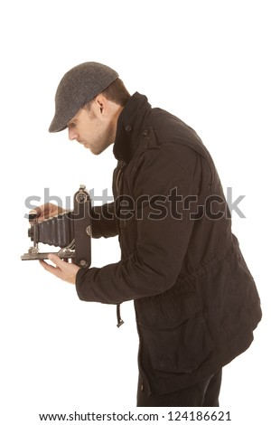 A man taking a picture with his old fashioned camera with a serious expression. - stock photo