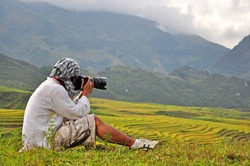 A man taking photo with digital camera in Sapa,Vietnam Concept about ready for landscape photography