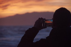 A man taking pictures of a vivid sunset with his smartphone on the beach