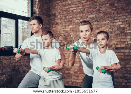 A man teaches his son self defense in a gym. Mom and daughter train with dumbbells while standing in the gym.  Stock photo ©