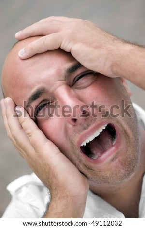 A man that looks distraught and mentally overloaded grabs his bald head in agony and desperation. Shallow depth of field.