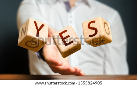 A man throws cubes with letters and makes up the word YES. Agreement and acceptance, answer the question. Courage and irresistibility, zeal forwards, consent. Confirmation and acceptance, approval Stock photo ©