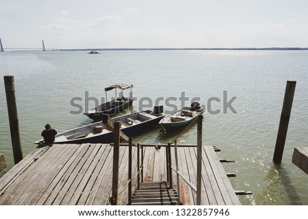 A man tie a rope to secure his boat to a wooden jetty. view from a wooden jetty #1322857946