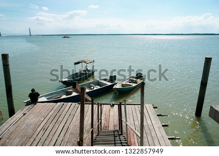 A man tie a rope to secure his boat to a wooden jetty. view from a wooden jetty #1322857949