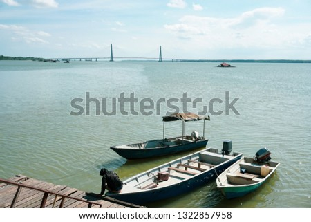A man tie a rope to secure his boat to a wooden jetty with johor bridge in the background. view from a wooden jetty #1322857958