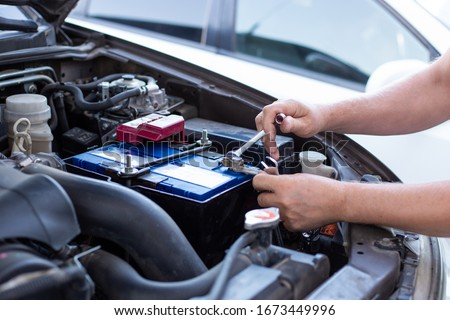 a man tightens with a wrench bolts for fastening a new battery, installing spare parts for a car Foto stock ©