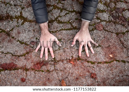 A man touches dirty, cracked and damaged asphalt ground with his fingers. #1177153822