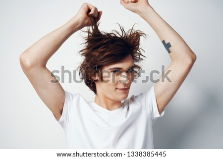 A man touches the hair on his head and looks into the camera                      #1338385445