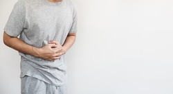 a man touching his stomach, on white background with copy space. Stomach pain and others stomach disease concept