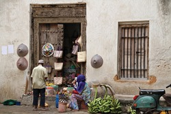 A man trades with a women on the street outside of her tiny shop in Stone Town, Zanzibar, Tanzania.