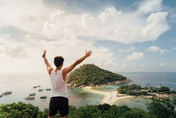 A Man Traveller Hands up at viewpoint on island,Travel Vacation Lifestyle summer Concept.Tropical paradise on the island of Koh nang yuan in Thailand,vintage tone