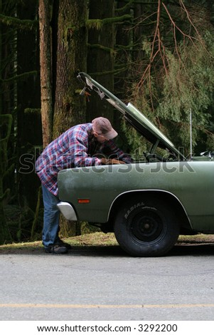 A man tries to figure out what is wrong with his car.