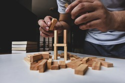 A man try to rebuild wooden blocks tower after them breakdown on white table