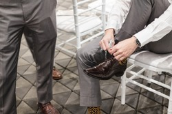 a man tying brown leather shoes with friends