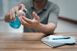 A man use hand sanitize cleaning hand and face mask on the wood table  Antivirus protection at work every day