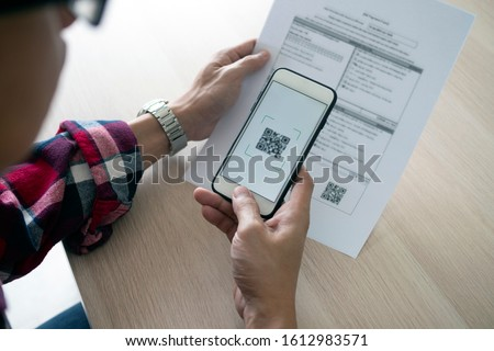A man uses a smartphone to scan the QR code to pay monthly credit card bills after receiving an invoice sent to home. Online bill payment concept