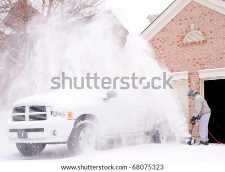 A man uses a snow blower to clear the freshly fallen snow off the driveway in front of his house in winter.