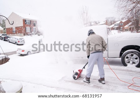 A man uses a snow blower to clear the freshly fallen snow off the sidewalk and driveway in front of his house in winter.