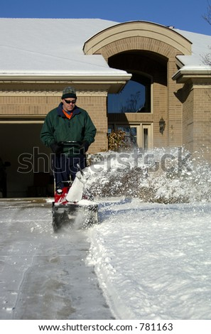 A man using a snowblower after a storm. 12MP camera, model released.