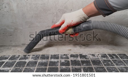 A man vacuums a construction site. Close-up of a cleaner in special clothing holding a brush from an industrial professional vacuum cleaner. A worker vacuums the bathroom floor before laying.