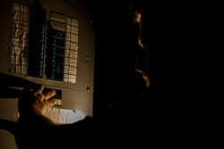 A man, visible only as a faint silhouette, is using a flashlight to investigate a home fuse box in his basement during a power outage.