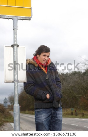 A man waiting at the bus stop on a cold windy day