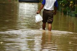 A man walk in high waters. Heavy rains caused floods in Bekasi, West Java/ Indonesia