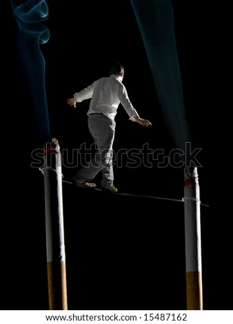 A man walking a tightrope suspended  between two big cigarettes. A conceptual image about the health risks of smoking.