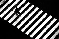 A man walking across zebra crossing on the street of Tokyo, Japan. This was shot from the top giving an interesting composition.