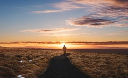 a man walking alone on footpath, Landscaped of Iceland, at Hvitserkur in Sunset