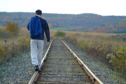 A man walking along train tracks