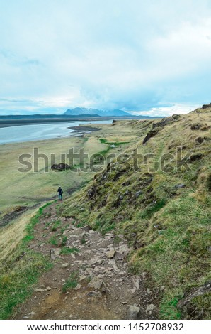 A Man walking at the green coast heading down to the beautiful black sand beach, in North Iceland, Europe.  #1452708932