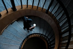 A man walking down the stairs with a cup of coffee in his hand.