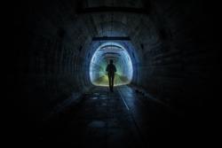 a man walking in a dark tunnel - MRU bunkers Poland