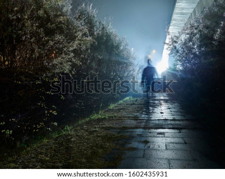 A man walking in the fog against the light generating a mystery silhouette