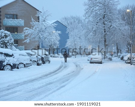 A man walking in the middle of the road during a snowstorm. Snow-covered pavements. Winter attack in Germany. Heavy snowfall in Heiligenhaus. Foto stock ©