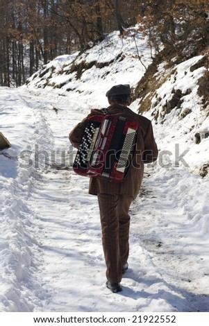 a man walking in the snow carrying his accordion