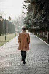 A man walking into the distance along a long street of a European city