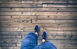 A man walking on aged wooden floor, point of view perspective.