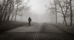 A man walks alone in the spooky fog in the winter forest, black and white