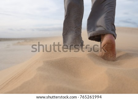 A man walks along the sandy beach. In the air, grains of sand fly from a strong wind. Photo close-up #765261994