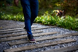 A man walks on a gravel wood path in a mountain forest